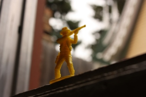 A plastic yellow toy cowboy takes aim on the windowsill